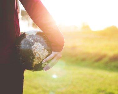 girl holding globe in a field